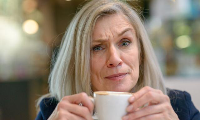 Puzzled or disbelieving middle aged woman looking at the camera with a sceptical frown as she enjoys a mug of coffee