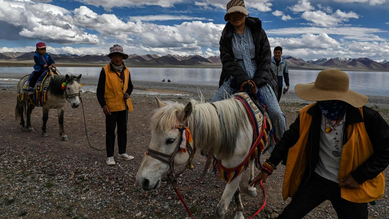 Photo shows a government organised media tour with tourists riding horses at Namtso lake in Dangxiong county, known in Tibetan as Damxung county, in China's Tibet Autonomous Region. Picture: Hector Retamal/AFP
