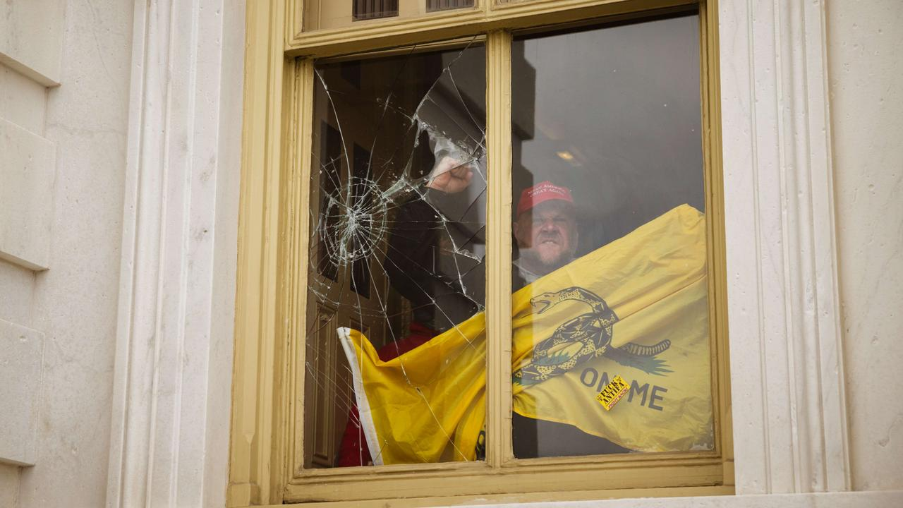 A member of a pro-Trump mob shatters a window with his fist from inside the Capitol Building after breaking into it in Washington. Picture: Jon Cherry/Getty Images/AFP