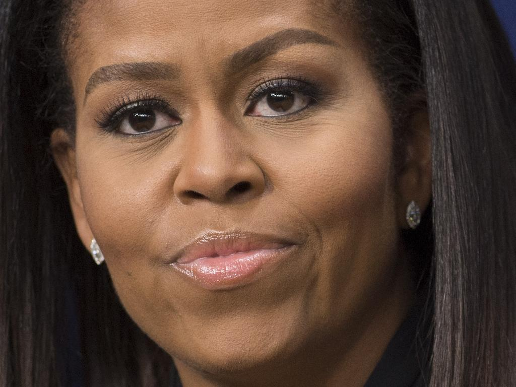 """(FILES) In this file photo US First Lady Michelle Obama speaks following a screening of the movie, """"Hidden Figures,"""" in the Eisenhower Executive Office Building adjacent to the White House in Washington, DC on December 15, 2016. - Donald Trump is a """"racist"""" president whose strategy of fearmongering, division and promoting ugly conspiracy theories could """"destroy"""" America if he is re-elected, former first lady Michelle Obama said October 6, 2020.In a 24-minute video offering closing arguments for Democratic White House nominee Joe Biden four weeks before election day November 3, Obama described Trump and his Republican allies as unfairly """"stoking fears"""" about African Americans. (Photo by SAUL LOEB / AFP)"""