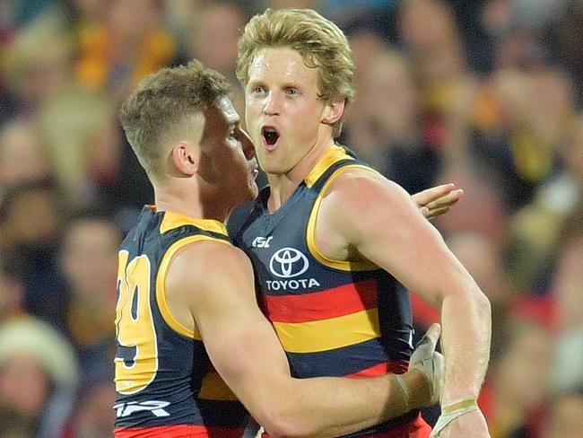 Rory Sloane of the Crows (right) reacts after kicking a goal.