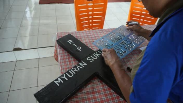 Andrew Chan and Myuran Sukamaran's crosses are stencilled by a mortician in Bali