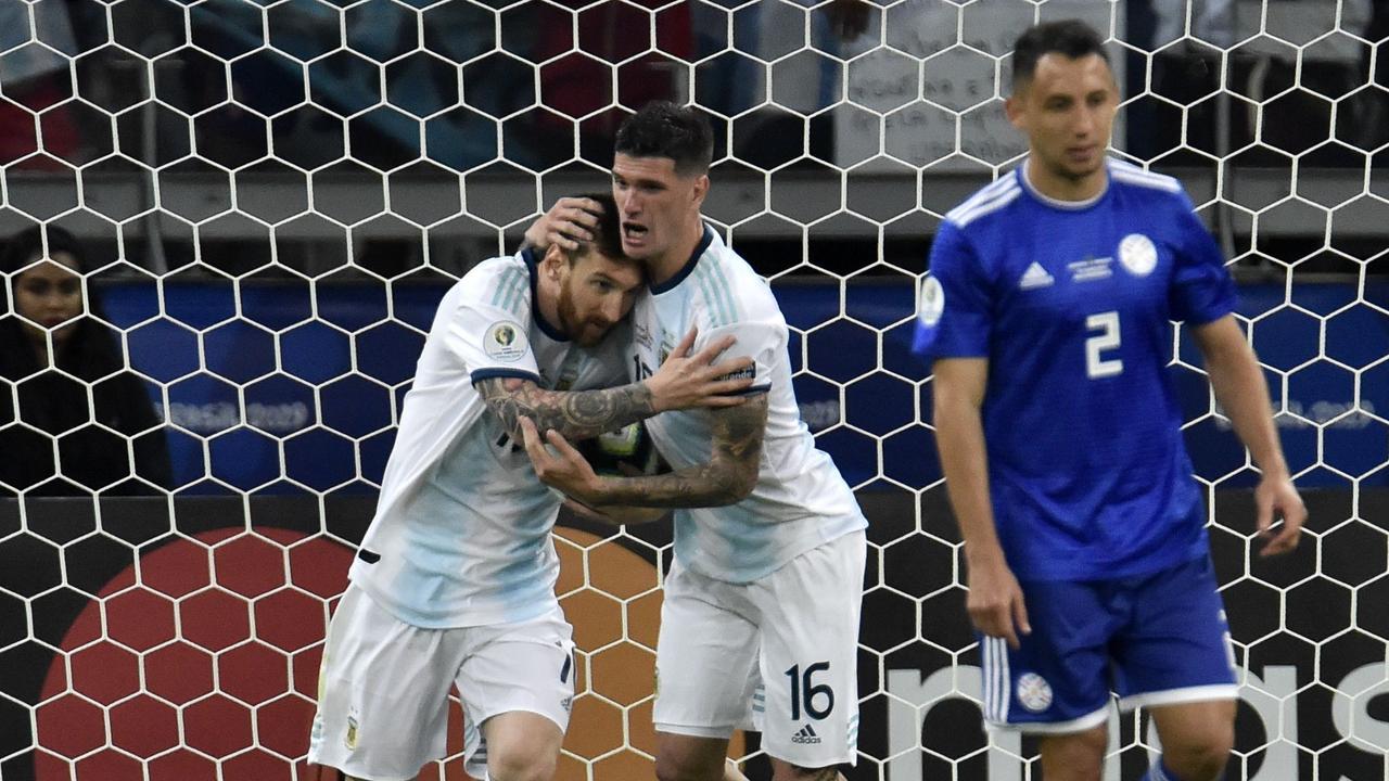 Argentina's Lionel Messi (L) celebrates with teammate Rodrigo De Paul after scoring a penalty