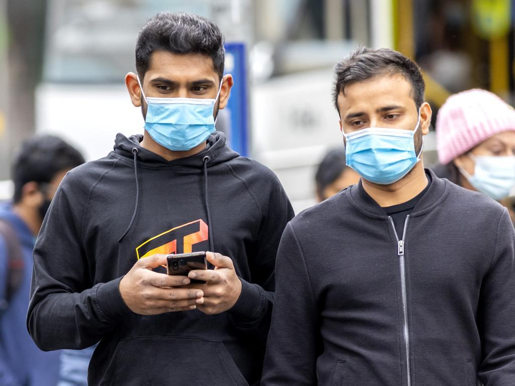 People get around Melbourne CBD wearing face masks.