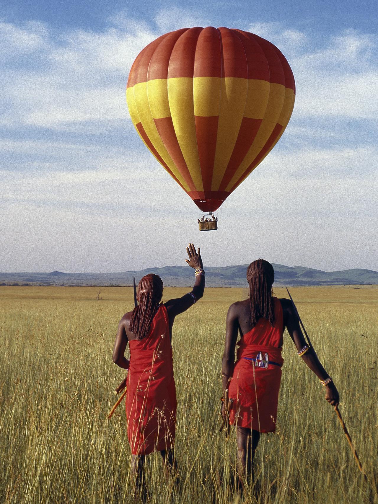 Masai warriors watch a hot-air balloon flight over Masai Mara