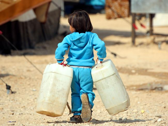 An Iraqi refugee child who fled Mosul carries jerry tanks at the UN-run Al-Hol refugee camp in Syria's Hasakeh province. Picture: AFP/DELIL SOULEIMAN