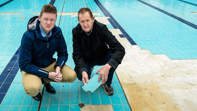 Tea Tree Gully councillor Lucas Jones and Mayor Kevin Knight with inspect the tiles coming loose on the bottom of Waterworld's 50m pool. Picture Roy Van Der Vegt/ AAP