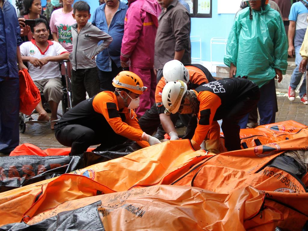 Rescuers try to identify victims at a makeshift mortuary in Carita. Picture: AFP
