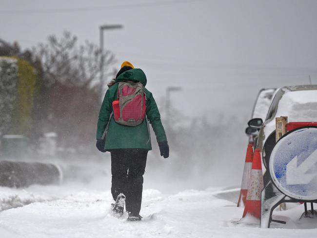 A woman walks through the snow in the village of Marsden. Picture: AFP/Oli Scarff