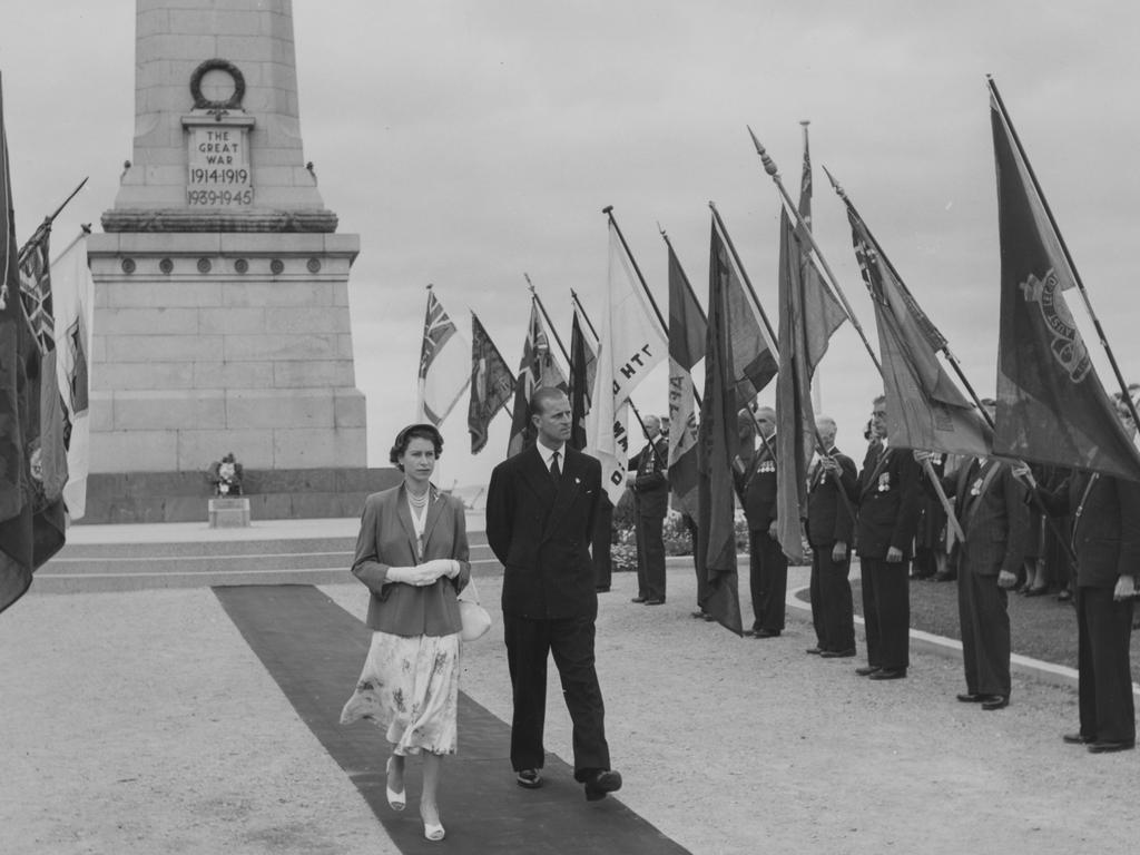 Queen Elizabeth II and Prince Philip walk past the standards of the ex-service men's associations after laying a wreath on the war memorial at Queen's Domain in Hobart, Tasmania on February 21, 1954. Picture: Paul Popper/Popperfoto/Getty Images)