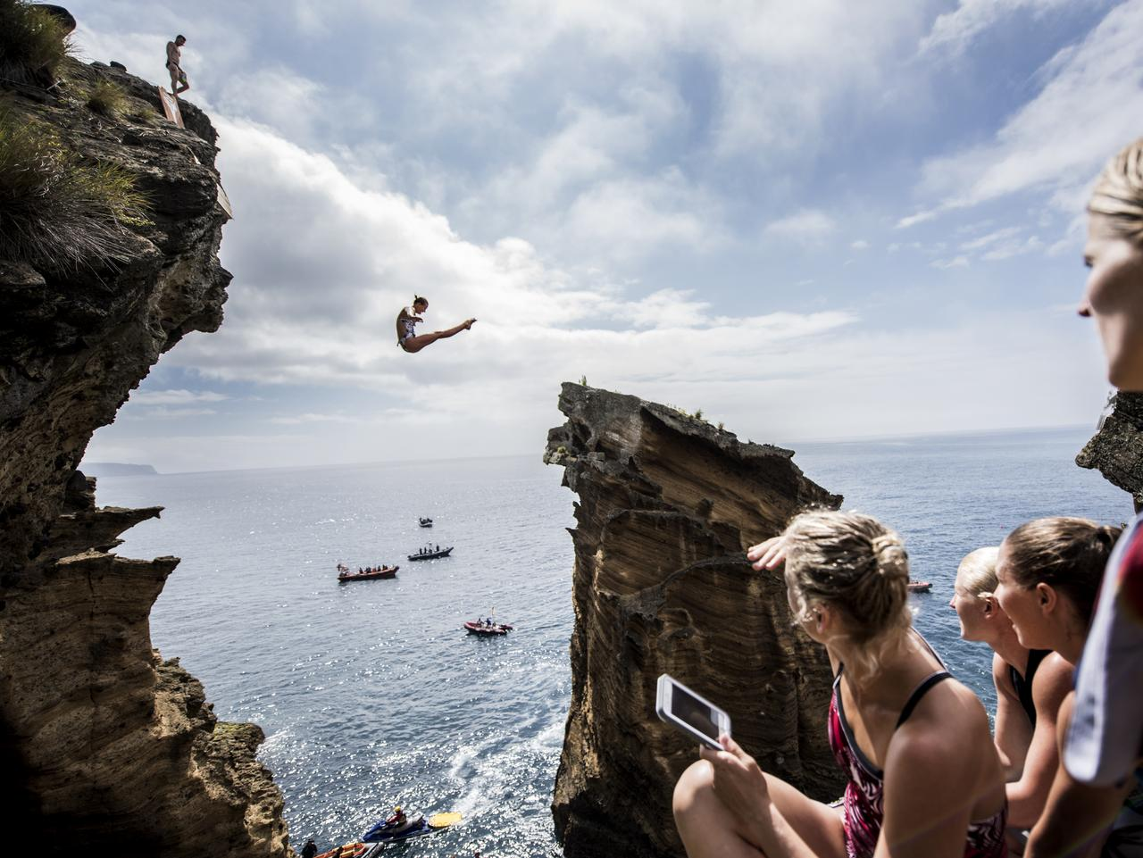 Rhiannan Iffland of Australia dives 20m from rock cliffs at Islet Franca do Campo while other divers watch on prior to third stop of the Red Bull Cliff Diving World Series, Sao Miguel, Azores, Portugal on July 7, 2016.