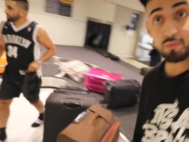 Saleh's friends stand at the luggage carousel in Sydney airport where they claim to be waiting for him to arrive in a suitcase. Picture: YouTube: Adam Saleh Vlogs