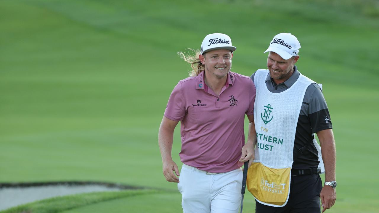 Cameron Smith of Australia smiles with caddie Sam Pinfold after blowing the first playoff hole.