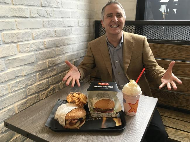 Jason Marker shows off some of the menu items at Carl's Jr. Picture: Darren Cartwright/AAP