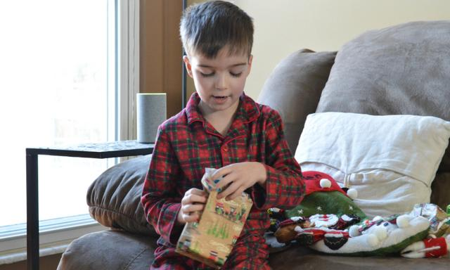 Young boy wearing Christmas pajamas and opening Christmas stocking gifts on a couch in a living room on Christmas morning