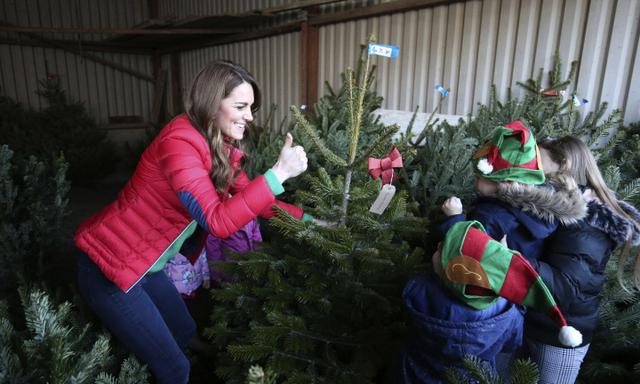 Britain's Kate the Duchess of Cambridge helped by children, moves a Christmas tree during a visit to Peterley Manor Farm where she took part in Christmas activities with families and children who are supported by the Family Action charity, in Buckinghamshire, England, Wednesday, Dec. 4, 2019. (Jonathan Brady/PA via AP)