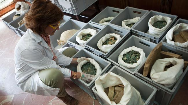 A woman opens a bag filled with Roman era bronze coins. Picture: AFP