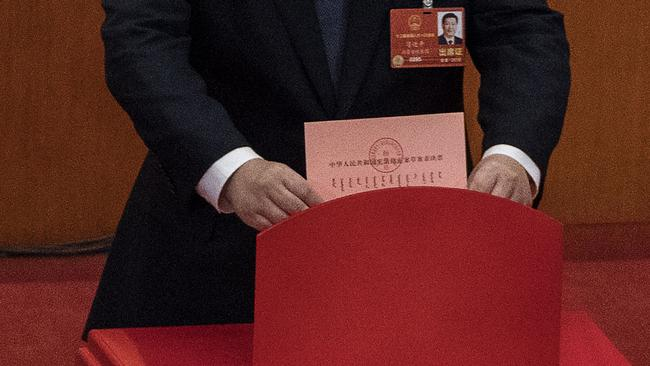 Mr Xi places his ballot in a box during a vote on an amendment to the constitution. Picture: Kevin Frayer/Getty Images