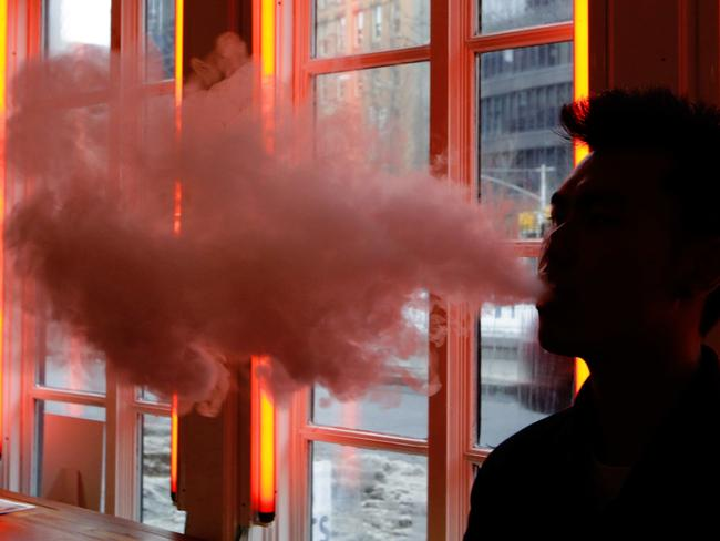 A customer exhales vapour from an e-cigarette at a store in New York. Picture: Frank Franklin II