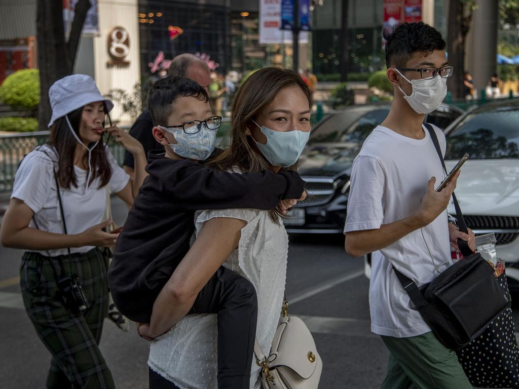 Demand for facemasks has surged, particularly in parts of Asia. Pictured, a Chinese family wearing face masks walk in a pedestrian crossing in Bangkok, Thailand. Picture: AP Photo/Gemunu Amarasinghe.