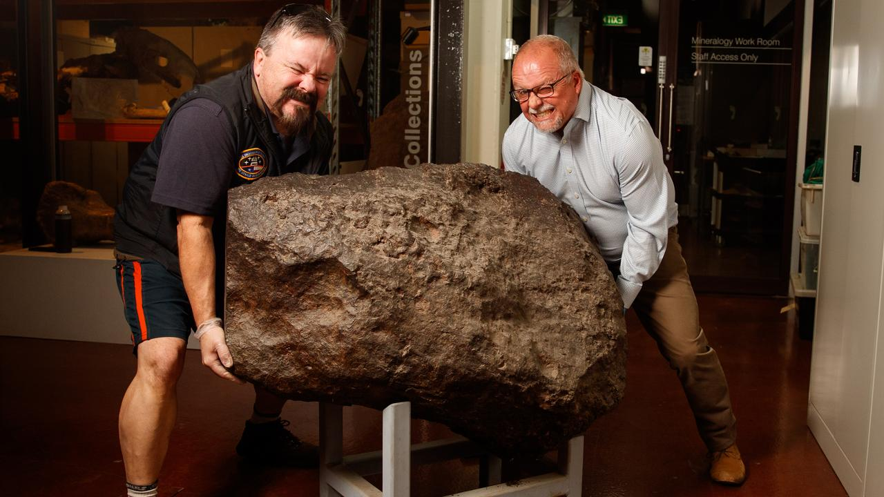 Paul Curnow from the Adelaide Planetarium with SA Museum earth sciences senior collections manager Ben McHenry pretending to lift the 1.4 tonne Huckitta meteorite.