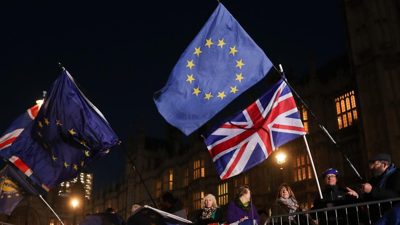 Anti-Brexit campaigners wave Union and EU flags outside the Houses of Parliament in central London. Picture: AFP