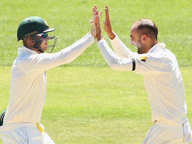 Nathan Lyon (right) celebrates the wicket of Rohit Sharma with Steve Smith.