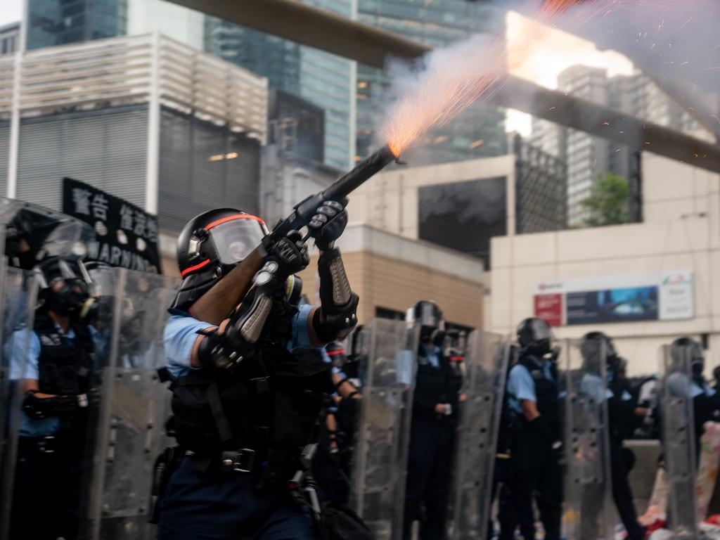 A police officer fires tear gas during a protest. Picture: Anthony Kwan/Getty