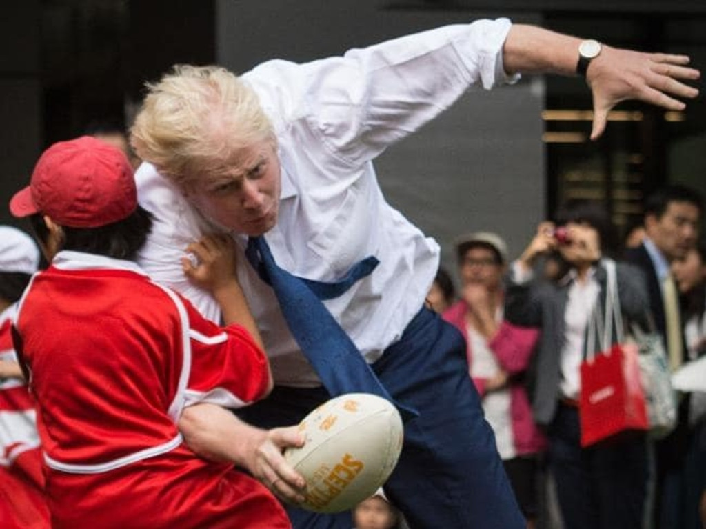 Boris Johnson tackles a Japanese schoolboy in a game of rugby.