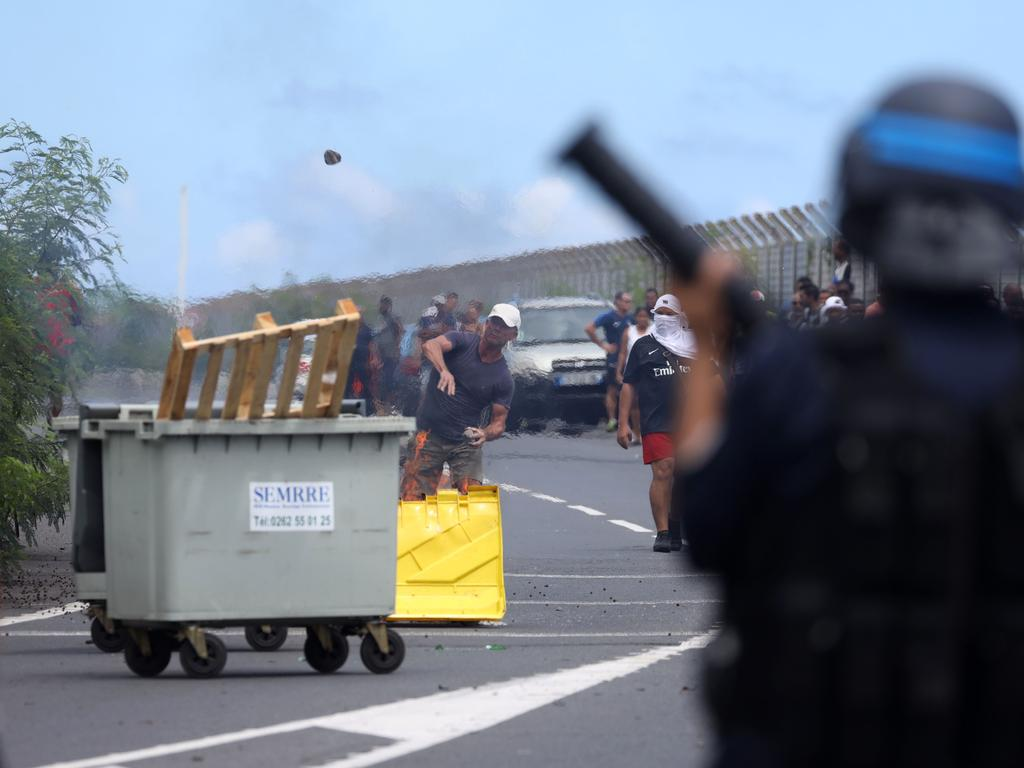 A demonstrator throws a stone as he faces French police officers in Le Port as people protest against the arrival of passengers from the Sun Princess cruise ship. Picture: Richard Bouhet/AFP