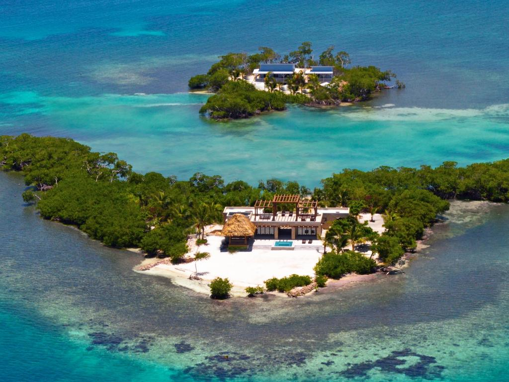 """ONE TIME WEB USE ONLY - FEE APPLIES FOR REUSE -  Aerial view. TAKE ALL-INCLUSIVE to the next level with a stay at this exotic private island for £2,200 per night. Incredible images show the 3000-square-foot luxury villa with comfortable chairs, glimmering pools and spacious rooms filled with natural light. Other striking shots show the paradise island from above with lush greenery surrounding the manmade resort and sparkling blue ocean waters off the coast of the island. Gladden Island lies directly on the edge of the widest and most picturesque section of the Belize Barrier Reef in the Caribbean Sea. Located 20 miles off the coast of Placencia, Belize, Gladden is the furthest island out from the mainland and closest to the protected side of the reef where the water is calm and clear. The magical """"Gladden Split"""" where the whale sharks congregate once a year is a mere few miles away. Exclusive use of the island costs around £2,200 for two people per night and £2,660 for four people per night, with a minimum four-night stay required. Gladden Private Island / mediadrumworld.com  Picture: Media Drum World"""