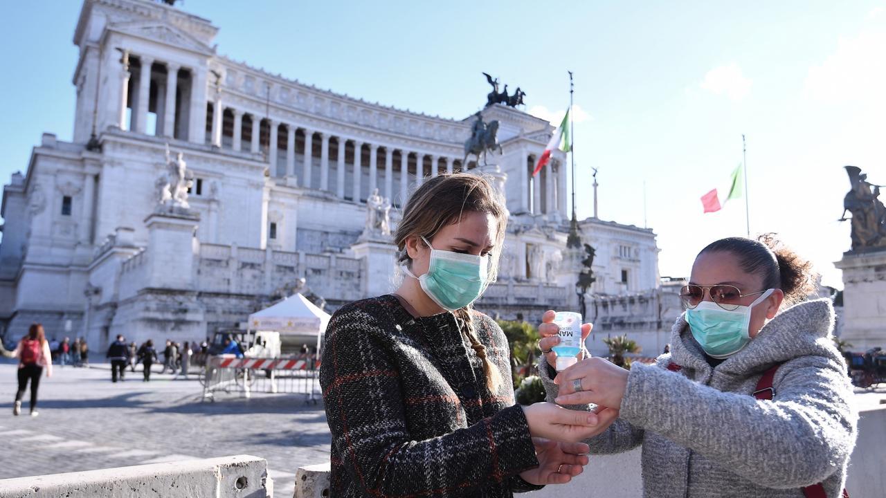 Women wearing face mask disinfect their hands in central Piazza Venezia, in Rome. Picture: Alfredo Falcone/LaPresse via AP.