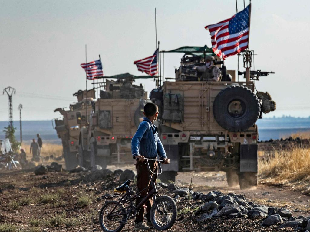 A Syrian boy on his bicycle looks at a convoy of US armoured vehicles patrolling fields on October 31, 2019. Picture: Delil Souleiman/AFP