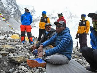 In this photograph taken on May 2, 2021, Nepal's mountaineer Kami Rita Sherpa (3R) performs a ritual after an interview with AFP at the Everest base camp in the Mount Everest region of Solukhumbu district, as Sherpa on May 7 reached the summit of Mount Everest for the 25th time, breaking his own record for most summits of the highest mountain in the world. (Photo by Prakash MATHEMA / AFP)