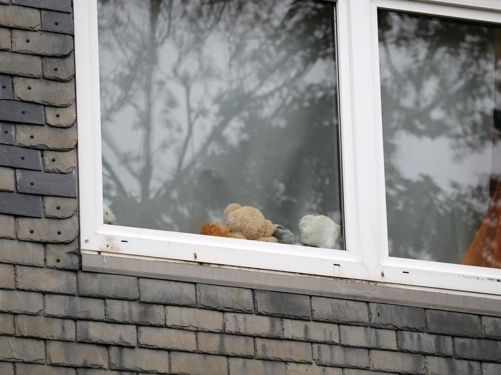 Stuffed animals are seen in the window of an apartment where five children were found dead. Picture: Andreas Rentz/Getty Images