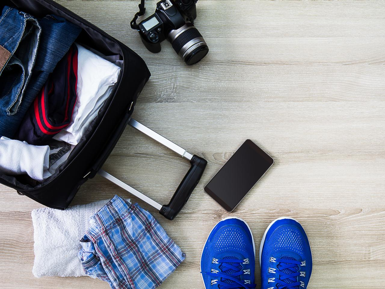 Traveling bag,camera,smartphone and men accessories on wooden background