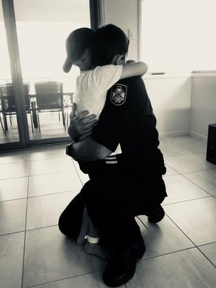 A Cairns police officer returns from work and hugs his young son who just spent eight days in hospital.