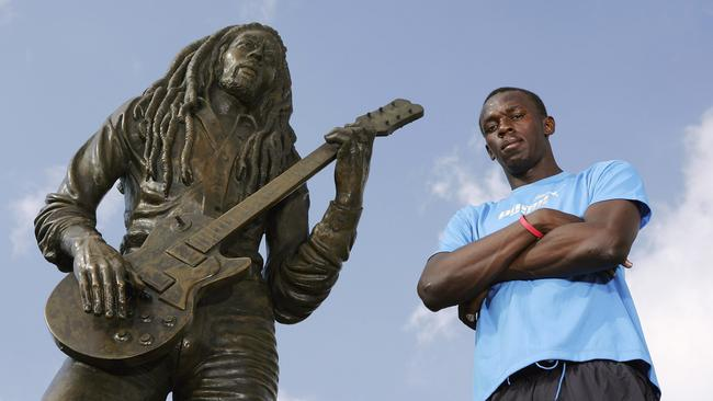 Usain Bolt beside a Bob Marley statue. Picture: Getty Images