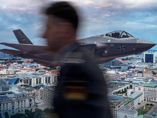 An unidentified participant walks past a poster advertising US defence equipment manufacturer Lockheed Martin's F-35 stealth multirole fighter at the 2017 Berlin Security Conference in Berlin. Picture: AFP