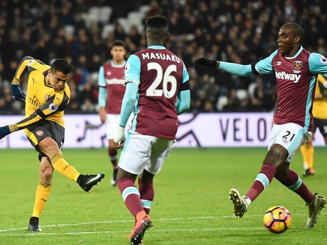 Arsenal's Chilean striker Alexis Sanchez (L) shoots to score their third goal.