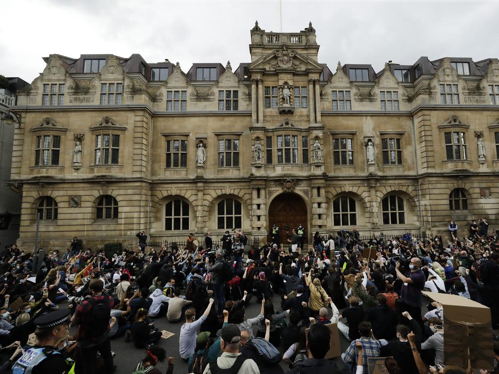 Protesters outside Oxford University with the statue of Cecil Rhodes above.