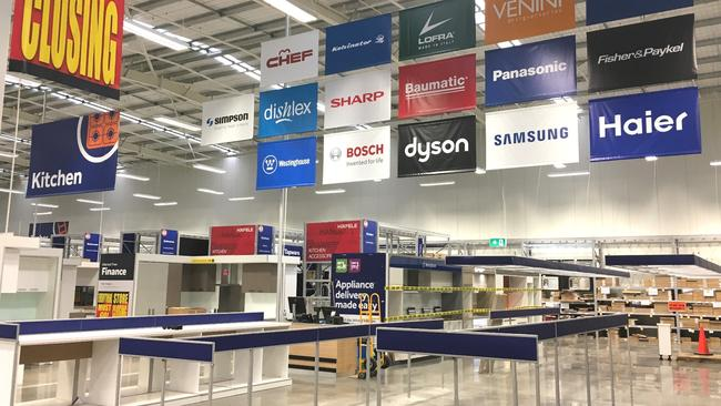 Signage advertising big brands hangs above empty aisles.