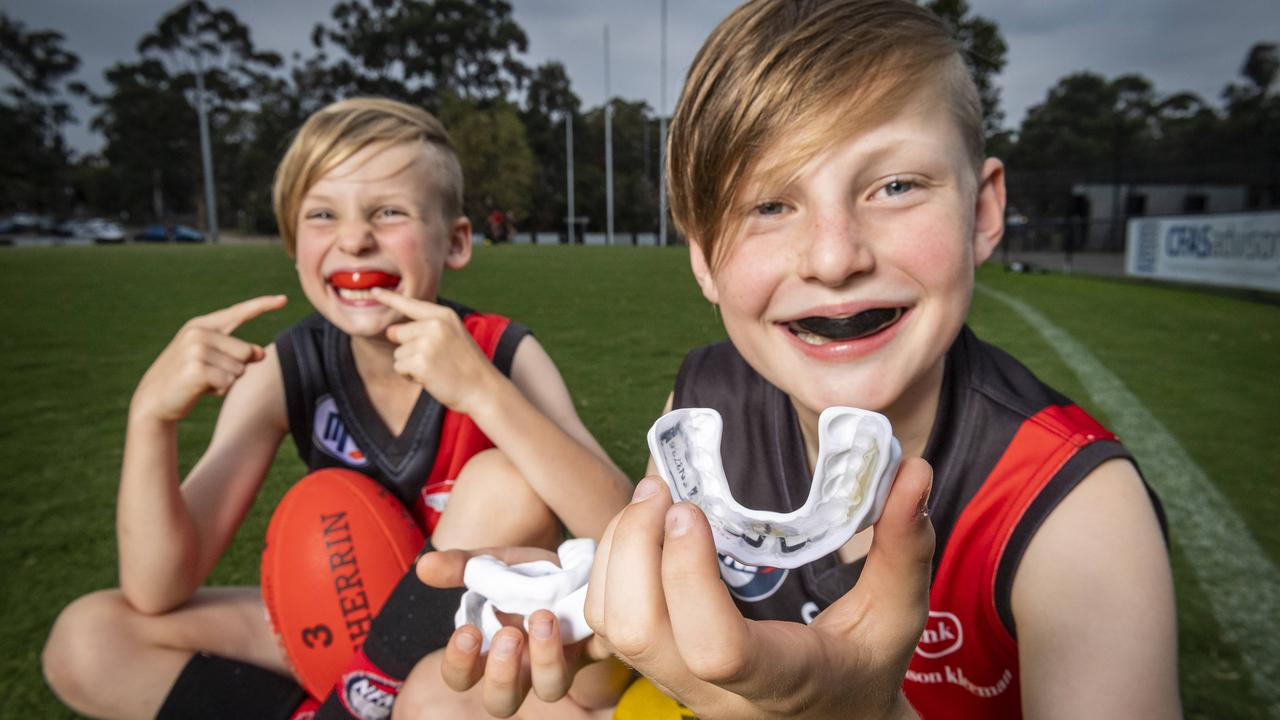 Harper Mai, 8 and Jonah Mai, 10, show off the new mouthguards with the data chip technology to monitor head knocks. Picture: Jake Nowakowski