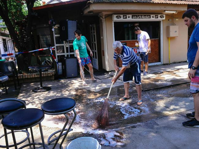 A man cleans the ground at a cafe after a man shot dead five people in the village of Zitiste, northern Serbia. Picture: AFP/Alexa Stankovic