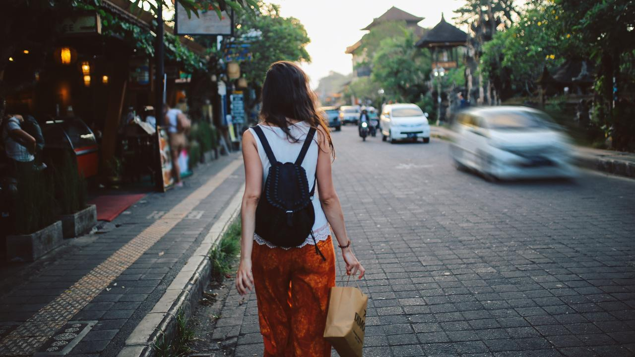Young woman with a backpack traveling in Bali, Indonesia. She is looking at the street markets that sell clothes and other souvenirs.
