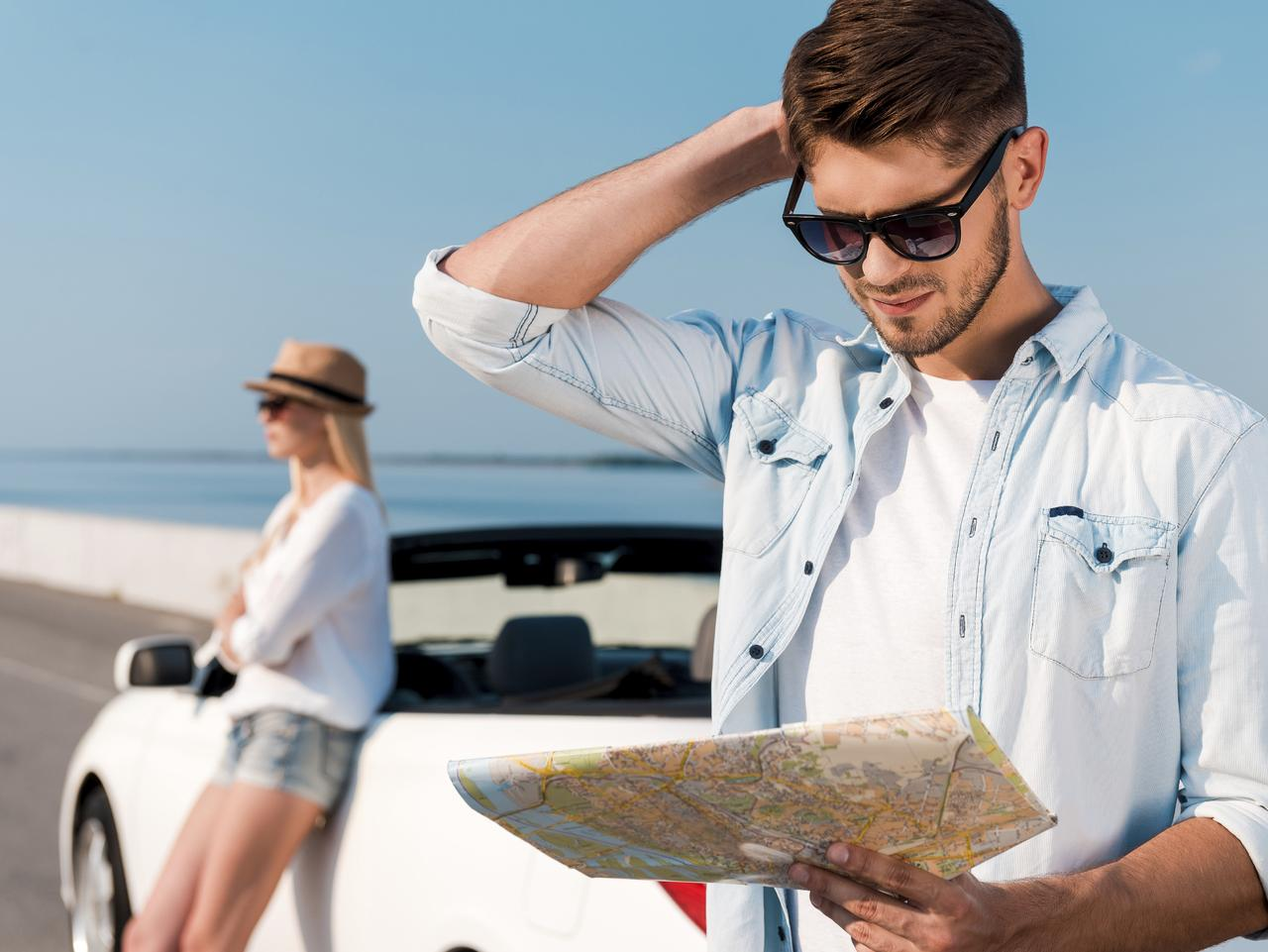 Trying to find their way. Frustrated young man examining map while his girlfriend leaning at their white convertible in the background. For Rod Chester column
