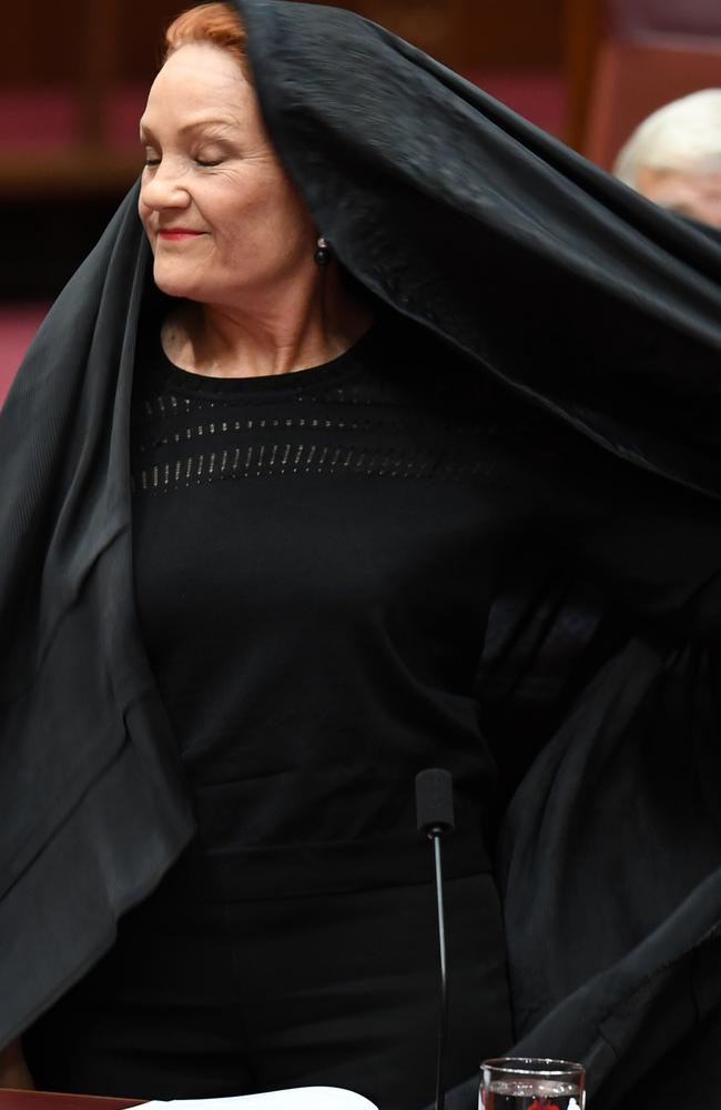 One Nation Senator Pauline Hanson takes off a burqa during Senate Question Time. Picture: AAP