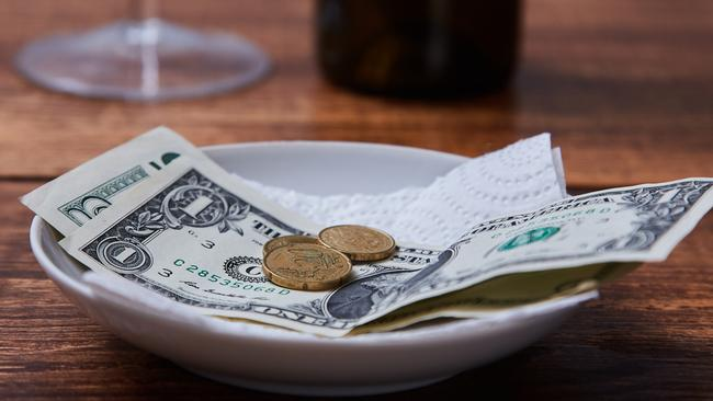 Restaurant tips or gratuity. Banknotes and coins on a plate.
