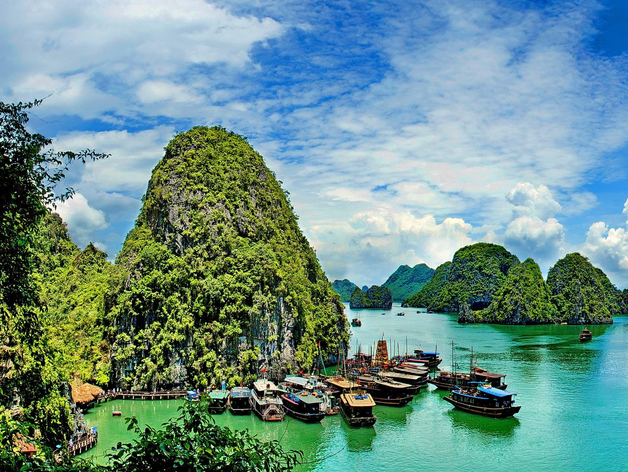 panorama on seascape with ships floats in a sea gulf Halong bay surrounded high mountains up on top from ocean water, direct rocks with green trees and cloudscape blue sky and clouds at sunny day, Ha Long Bay, Vietnam