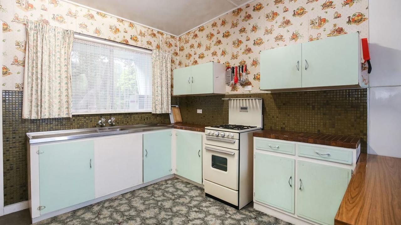 Brown tiled benchtops and pastel cabinetry.